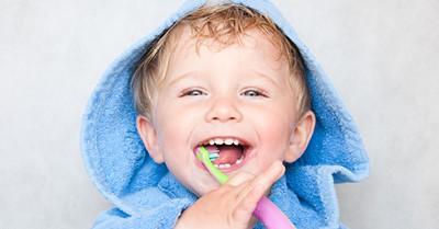 toddler boy smiling and brushing his teeth