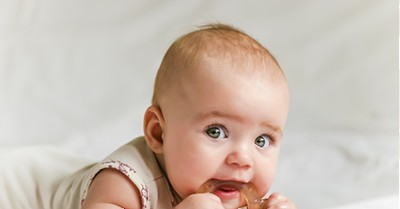 baby with teething ring in mouth