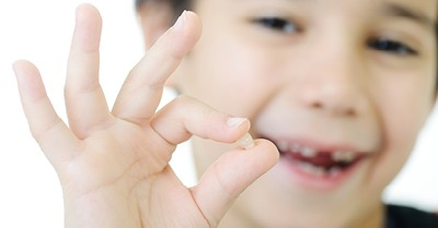 young boy holding his lost tooth