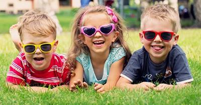 three children lying in grass wearing sunglasses