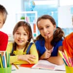 four children in classroom smiling