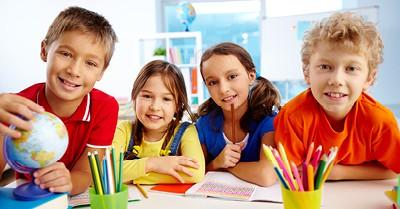 four children in classroom smiling