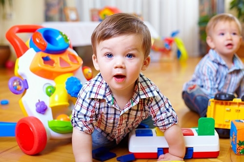 toddlers on floor playing with toys