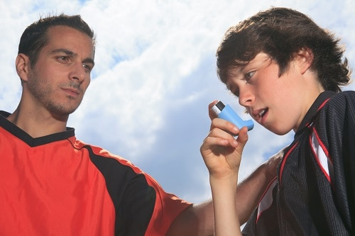 soccer player using his inhaler standing with his coach