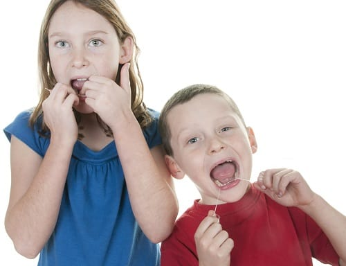 little girl and boy flossing teeth together