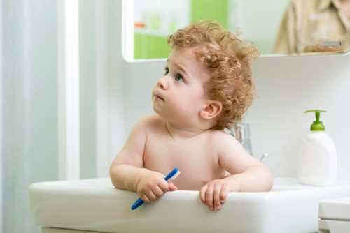 baby in sink holding toothbrush