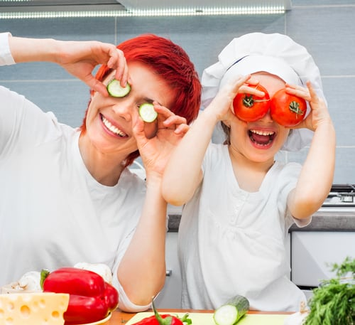 mother and daughter having fun with vegetables in kitchen