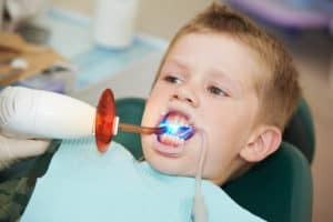child in dental chair getting dental filling