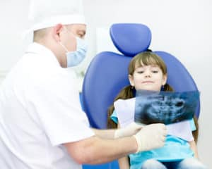 male dentist looking at dental x-ray with little girl