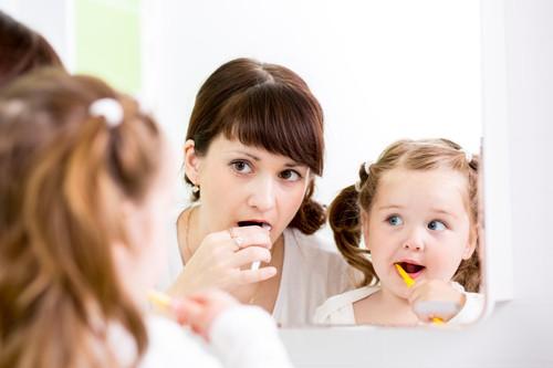 woman and little girl brushing teeth in mirror