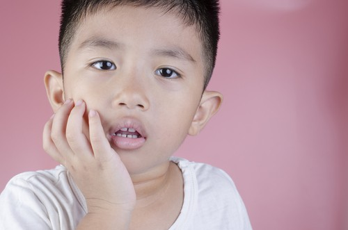 little boy holding mouth with toothache