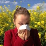 Girl sneezing with tissue - field of flowers in background