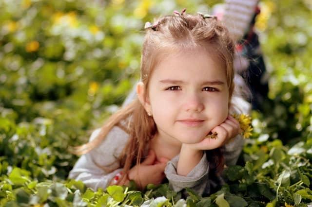 Little girl smiling, lying in field