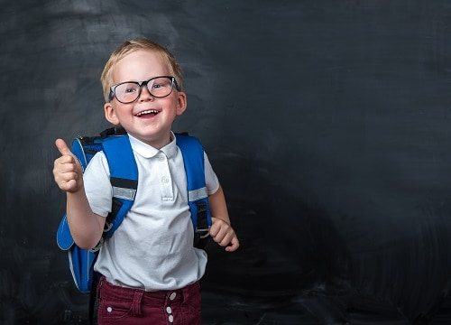 young boy with backpack giving thumbs up