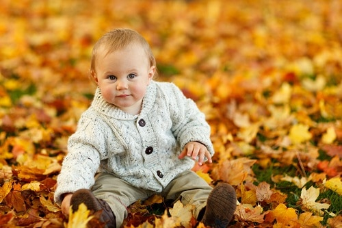 baby outside sitting in leaves