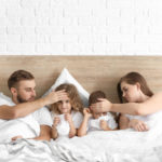 family in bed with sick kids
